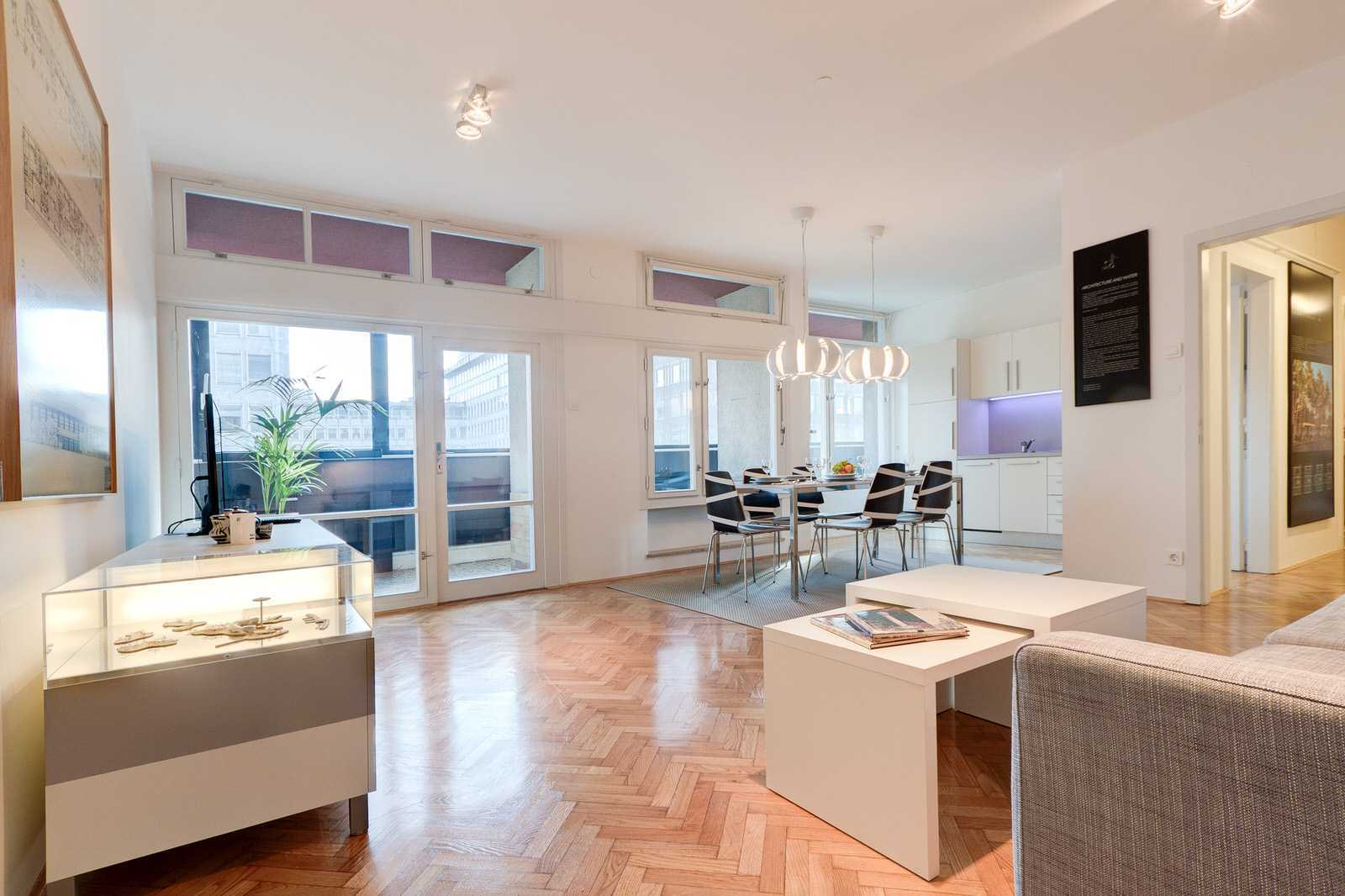 Ljubljana rental apartment's spacious living room with architectual projects displayed on the wall.
