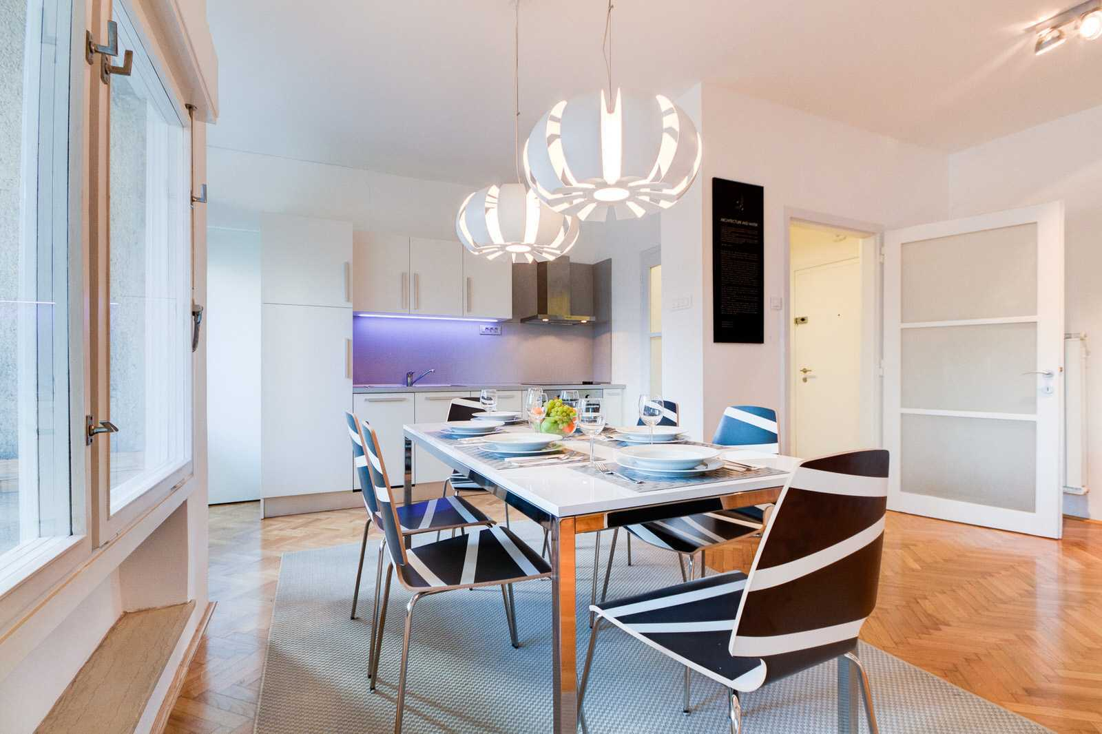 Dining table for 6 with modern pending lights and a fully stocked kitchen.