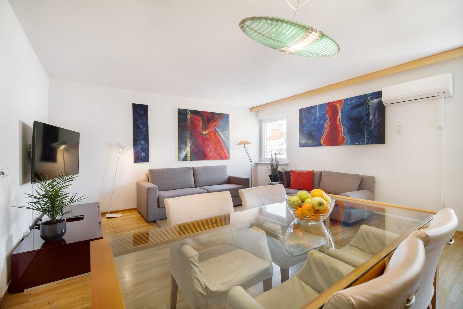 Ljubljana rental apartment Dalmatinova - living area with a big flat screen TV with cable channels and other features.