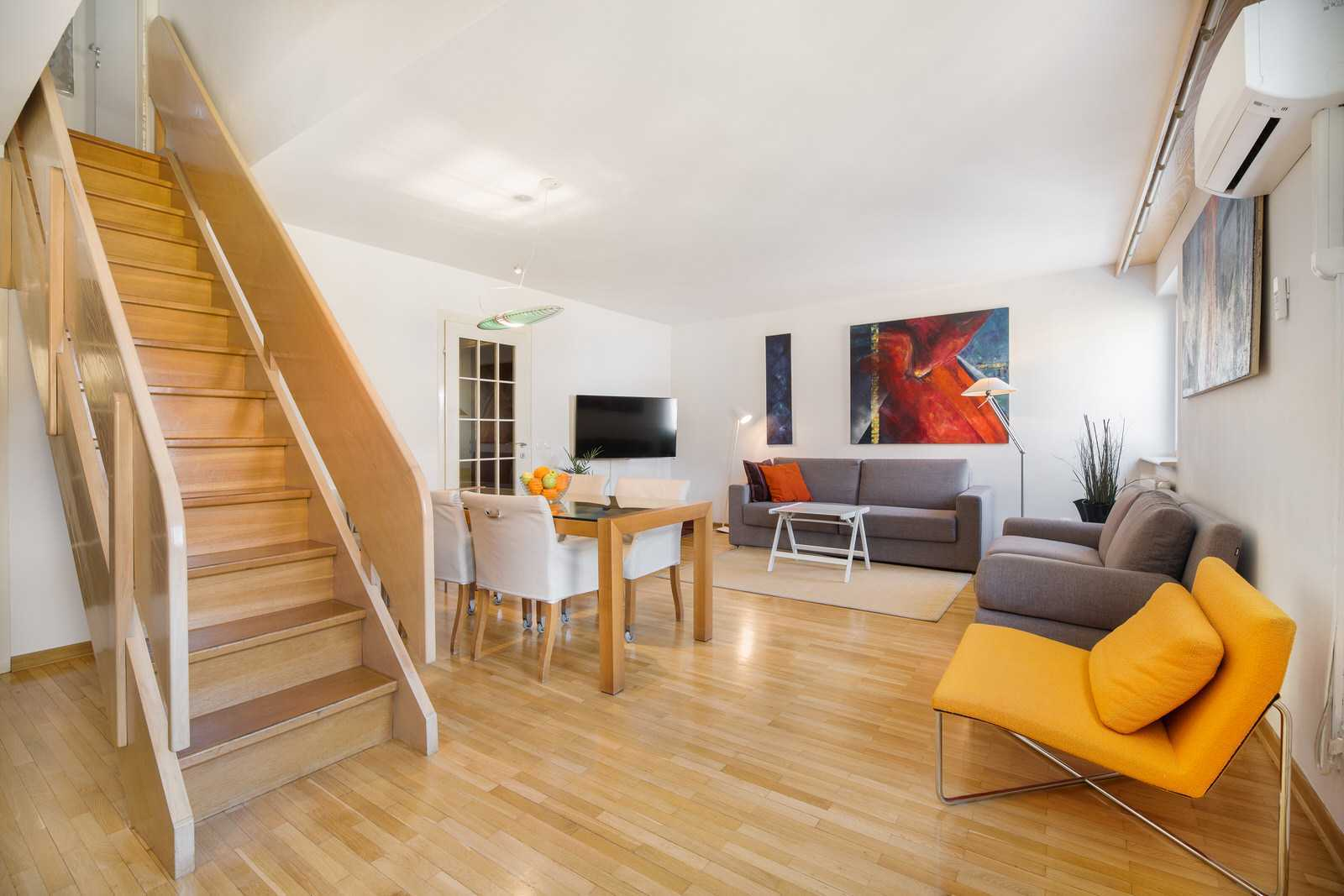 Ljubljana rental apartment Dalmatinova - open space living area with stairs leading upstairs to the master bedroom and sleeping niche.