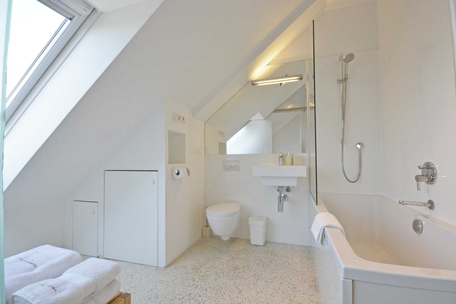 Ljubljana Mini Duplex's rental apartment bathroom with a bathtub and floor heating.