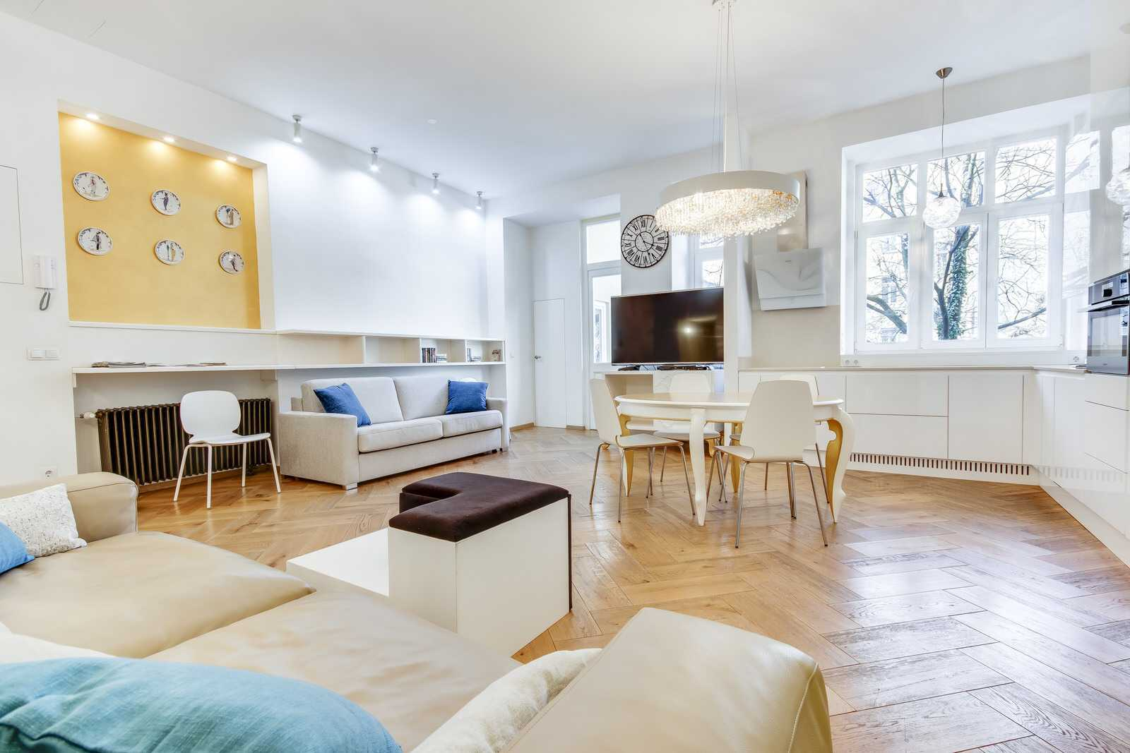 Open space living area with a flat screen TV and a small library with English literature.