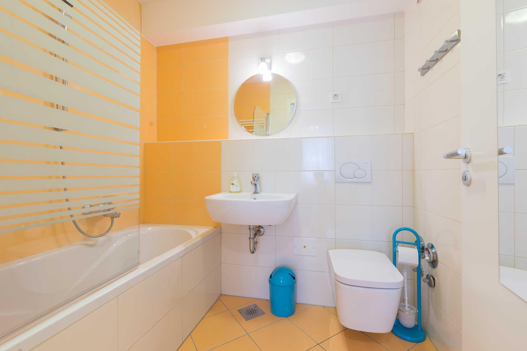 The bright bathroom has a shower/bathtub.