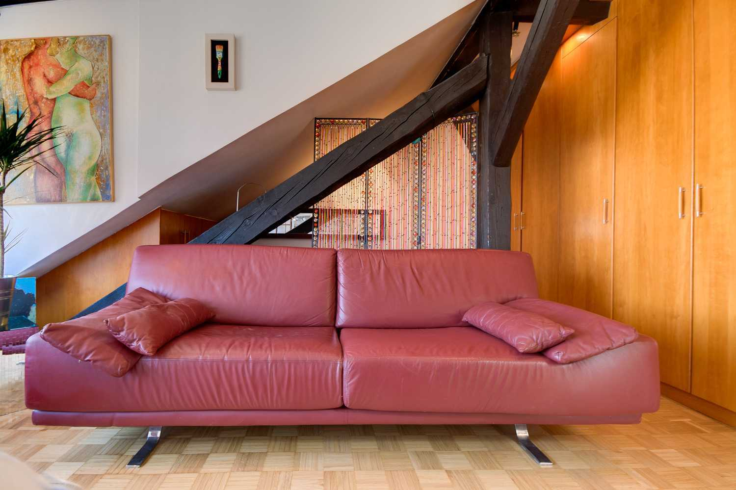 The living room has large red leather sofa.