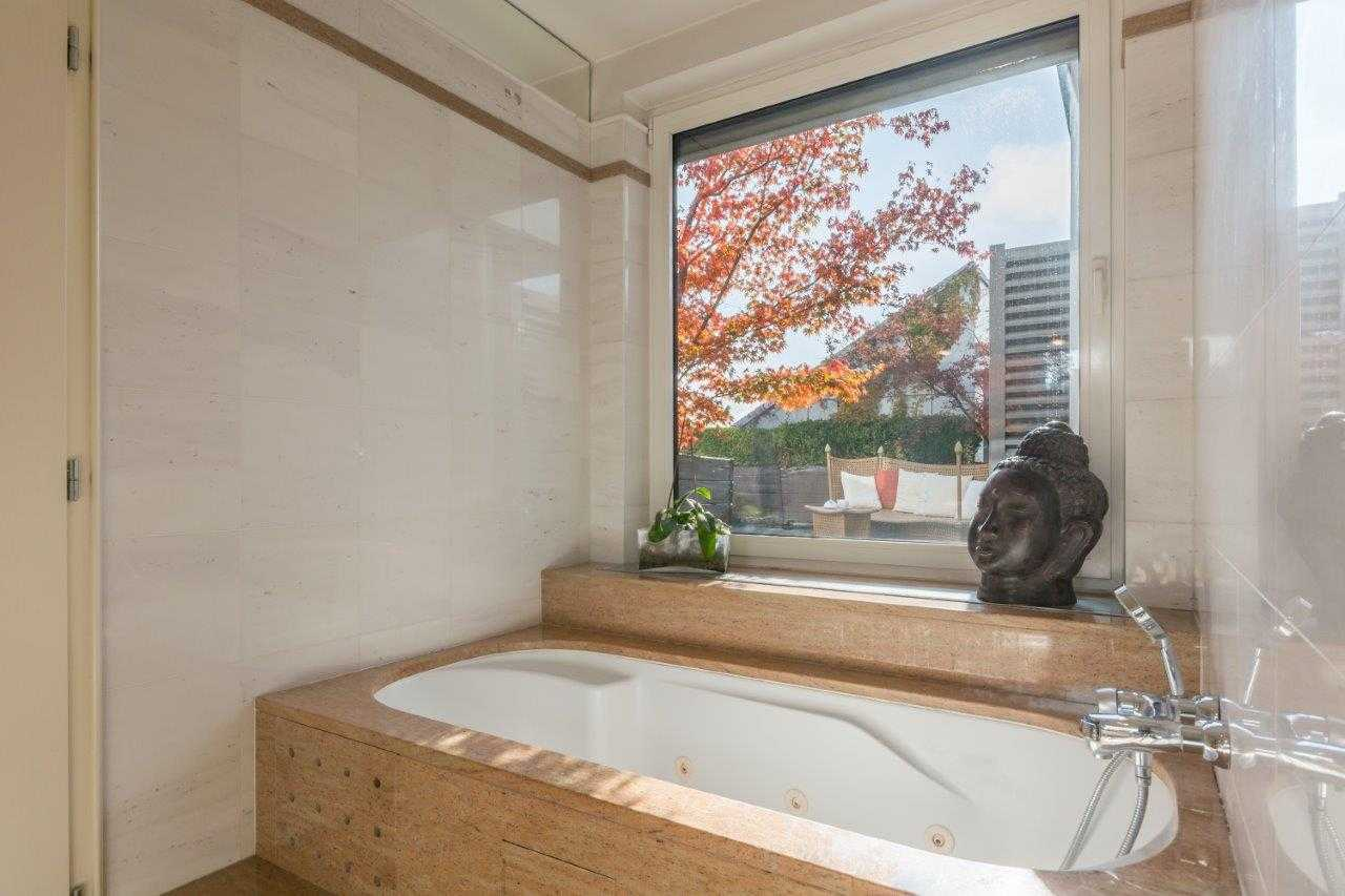 The large bathtub has a view of the penthouse terrace.