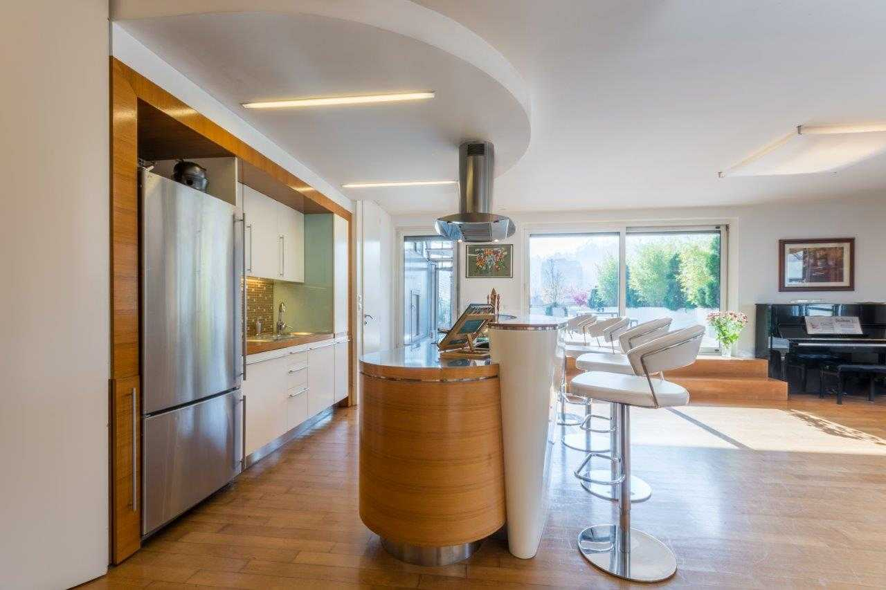 The kitchen has a large fridge and lots of cooking surfaces.
