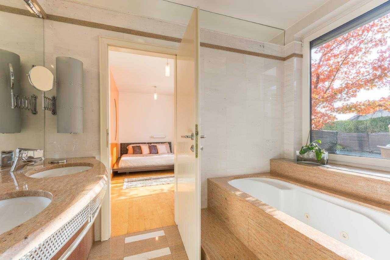 The bathroom features a large marble bathtub with a view of the outside terrace.