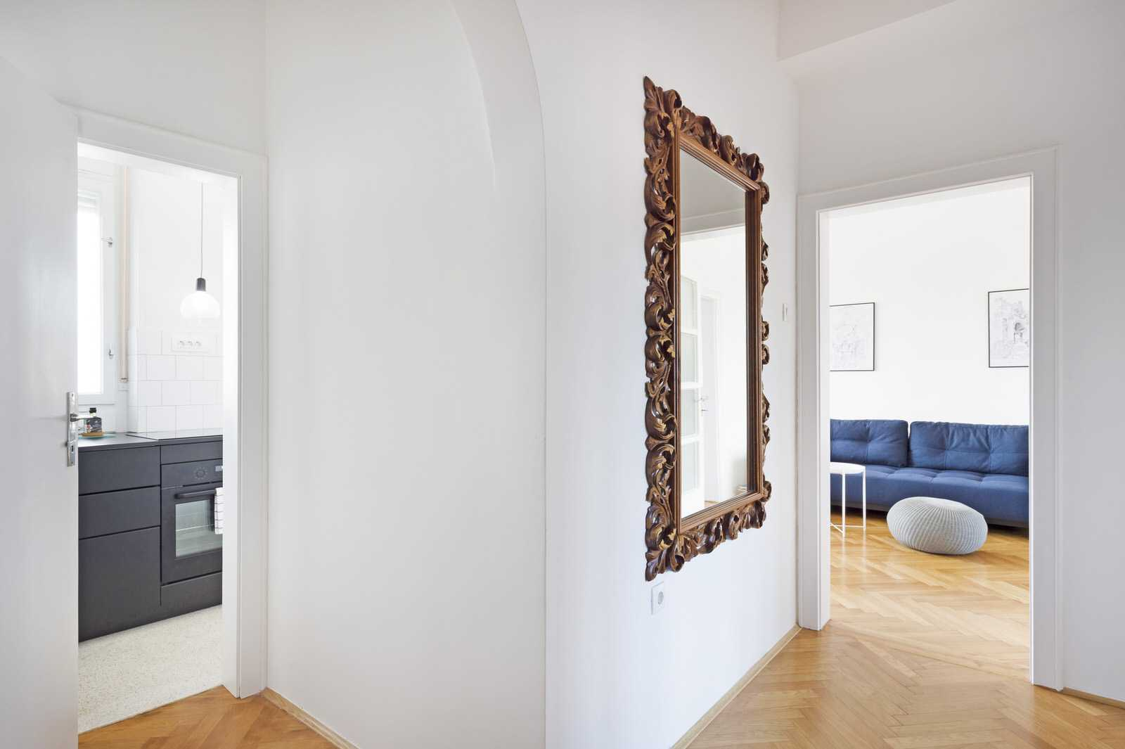 Apartment hallway with a rustic looking mirror.