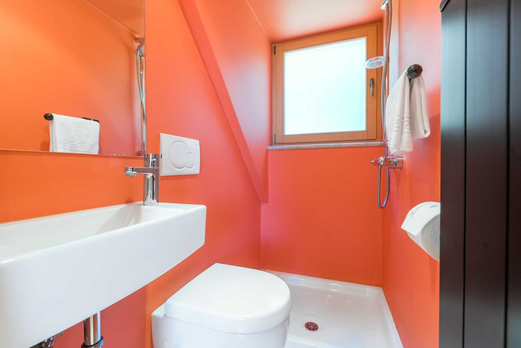 The bright orange bathroom features a walk in shower.