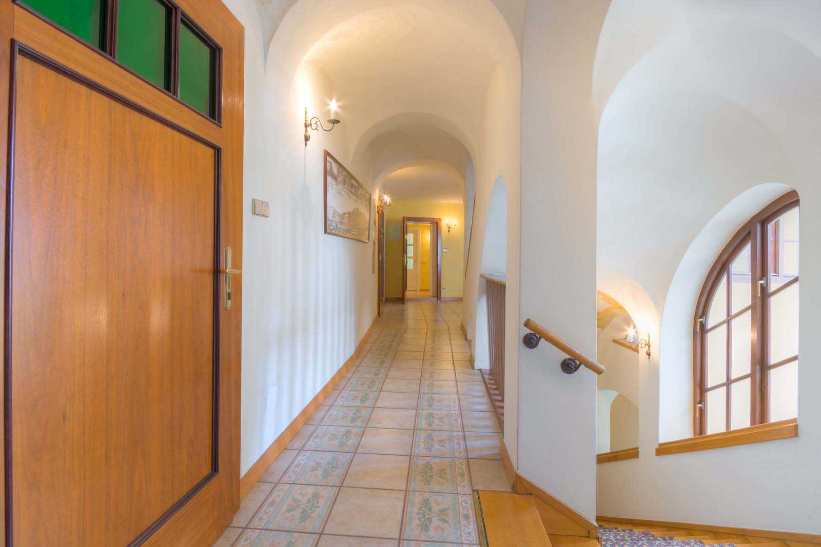 The hallway features rounded arches and tiled floors.