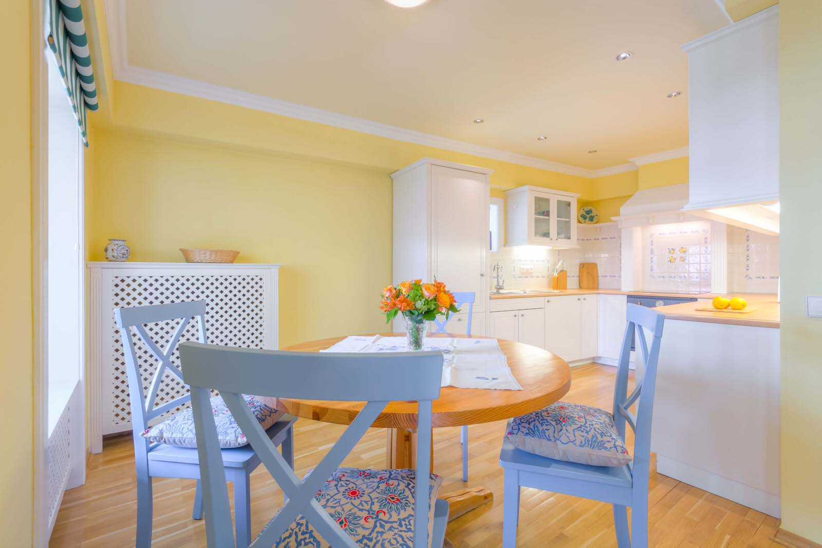 The kitchen has Mediterranean vibe with pastel yellow and blue colours.